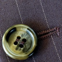 a button and buttonhole on a pin-striped suit