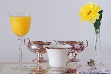 a china teacup, crystal vase, and silver cream and sugar set