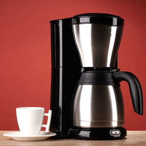 a coffeemaker with a coffee cup and saucer