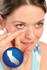 california a young woman inserting a contact lens