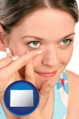 colorado a young woman inserting a contact lens