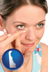 delaware a young woman inserting a contact lens