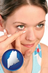 maine map icon and a young woman inserting a contact lens