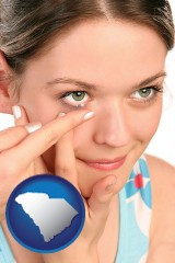 south-carolina map icon and a young woman inserting a contact lens