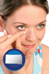 south-dakota map icon and a young woman inserting a contact lens