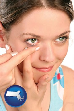 a young woman inserting a contact lens - with Massachusetts icon