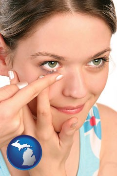 a young woman inserting a contact lens - with Michigan icon