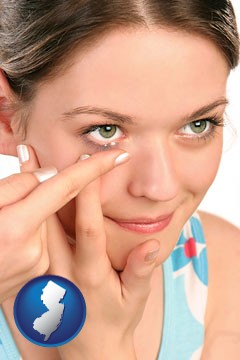 a young woman inserting a contact lens - with New Jersey icon