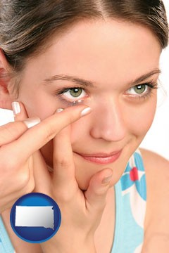a young woman inserting a contact lens - with South Dakota icon