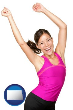 a happy young woman wearing fitness clothing - with North Dakota icon