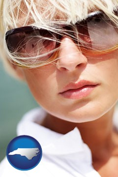 a young woman wearing sunglasses - with North Carolina icon
