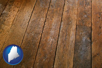 a distressed wood floor - with Maine icon