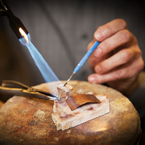 a goldsmith making a custom gold ring