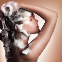 a woman washing her hair with shampoo