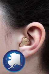 alaska map icon and a woman wearing a hearing aid in her left ear