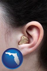 florida map icon and a woman wearing a hearing aid in her left ear