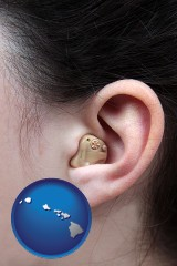 hawaii map icon and a woman wearing a hearing aid in her left ear