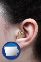 iowa map icon and a woman wearing a hearing aid in her left ear