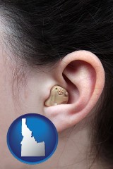 idaho map icon and a woman wearing a hearing aid in her left ear