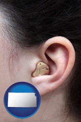 kansas map icon and a woman wearing a hearing aid in her left ear