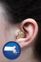 massachusetts map icon and a woman wearing a hearing aid in her left ear