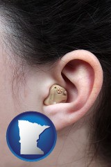 minnesota map icon and a woman wearing a hearing aid in her left ear