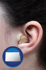 north-dakota map icon and a woman wearing a hearing aid in her left ear