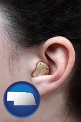 nebraska map icon and a woman wearing a hearing aid in her left ear