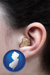 new-jersey map icon and a woman wearing a hearing aid in her left ear