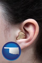 oklahoma map icon and a woman wearing a hearing aid in her left ear