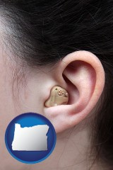oregon map icon and a woman wearing a hearing aid in her left ear