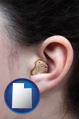 utah map icon and a woman wearing a hearing aid in her left ear