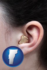 vermont map icon and a woman wearing a hearing aid in her left ear