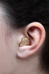 a woman wearing a hearing aid in her left ear
