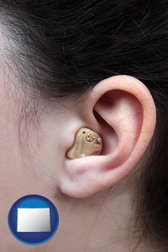 a woman wearing a hearing aid in her left ear - with Colorado icon