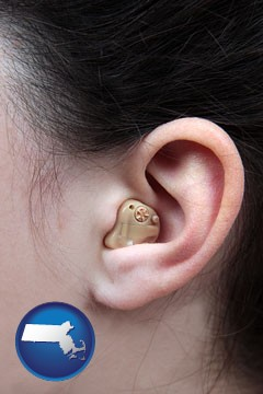 a woman wearing a hearing aid in her left ear - with Massachusetts icon