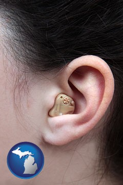a woman wearing a hearing aid in her left ear - with Michigan icon
