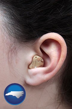 a woman wearing a hearing aid in her left ear - with North Carolina icon