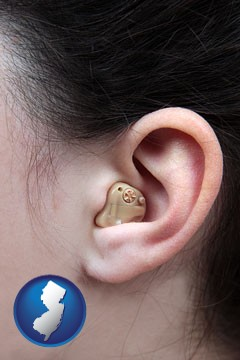 a woman wearing a hearing aid in her left ear - with New Jersey icon