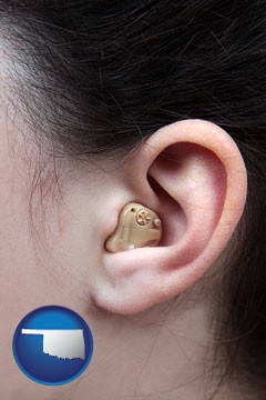 a woman wearing a hearing aid in her left ear - with Oklahoma icon