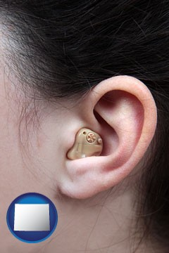 a woman wearing a hearing aid in her left ear - with Wyoming icon