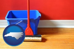 north-carolina map icon and a bucket and mop on a hardwood floor