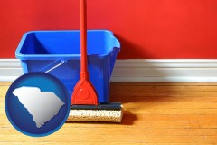 south-carolina map icon and a bucket and mop on a hardwood floor