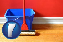 vermont map icon and a bucket and mop on a hardwood floor