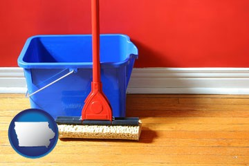 a bucket and mop on a hardwood floor - with Iowa icon