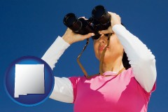 new-mexico map icon and a woman looking through binoculars