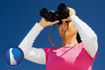 a woman looking through binoculars - with Delaware icon