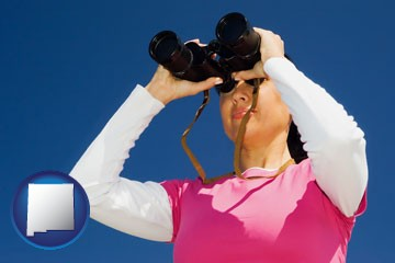 a woman looking through binoculars - with New Mexico icon