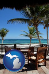 michigan map icon and outdoor furniture on a tropical, oceanfront deck