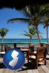 new-jersey map icon and outdoor furniture on a tropical, oceanfront deck